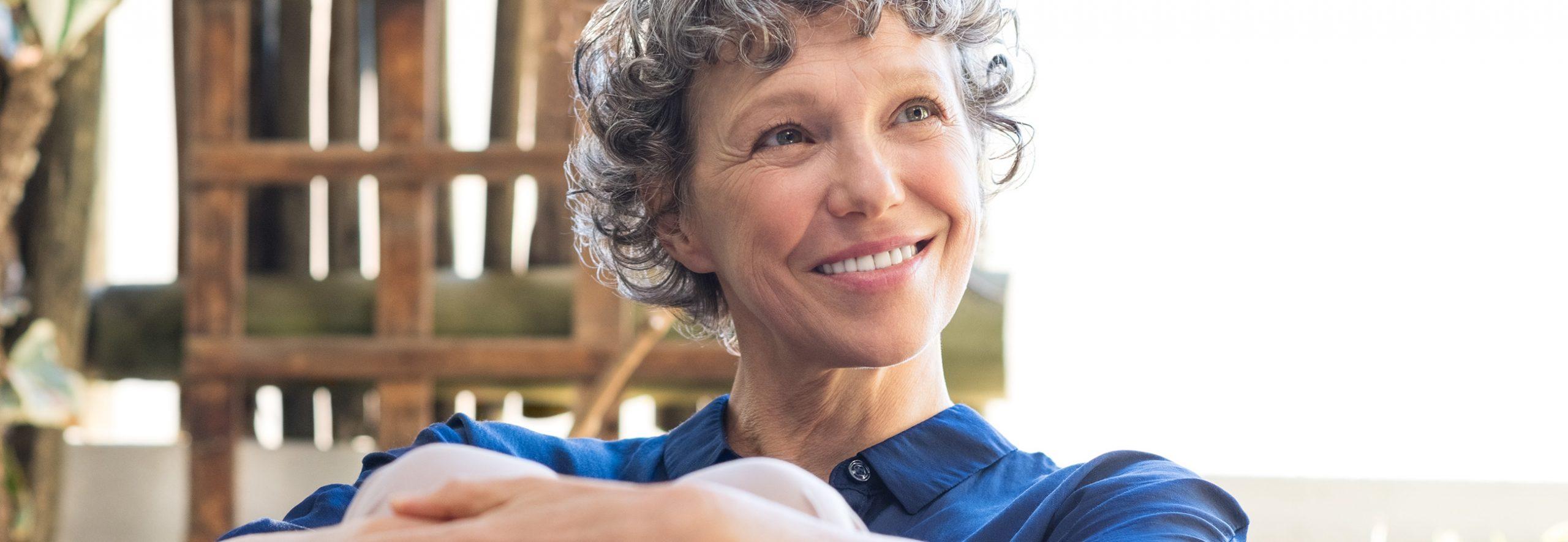 Frau lächelt mit Keramikimplantaten gesund und schön.