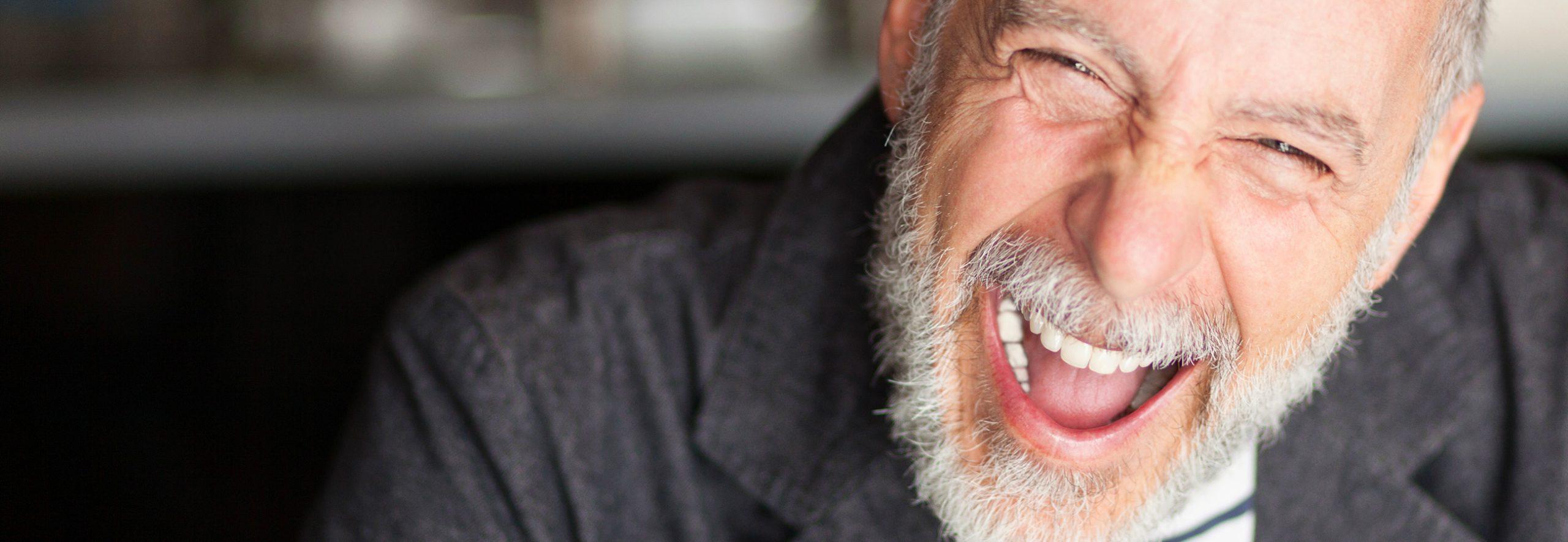 Mann lacht mit Zahnimplantaten aus Sauerlach